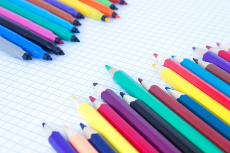 diagonally: The felt pens and pencils placed diagonally on the sheet with cells