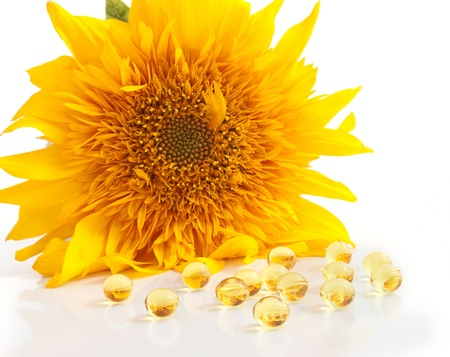 The sunflower and capsules with vitamins A and E on foreground