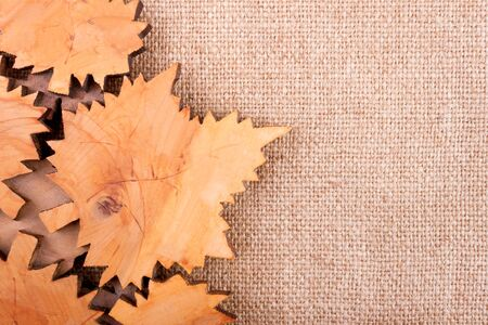 sheeted: Autumn background made by burlap and carved wooden leaves