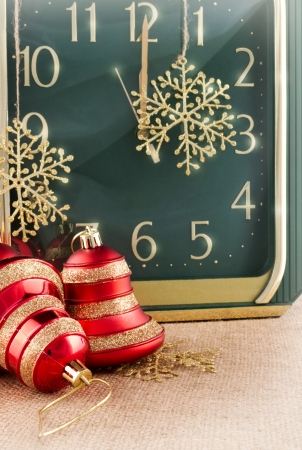 Holidays image with big watch in a second before New Years midnight with snowflakes and toys photo