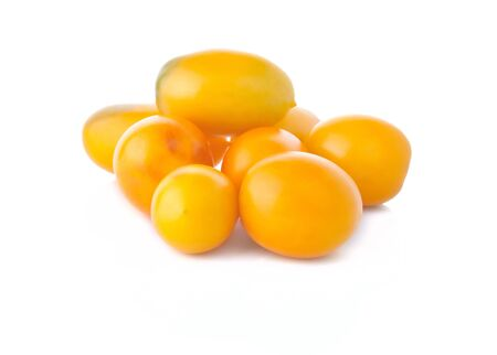 The heap of yellow tomatoes on the white background photo