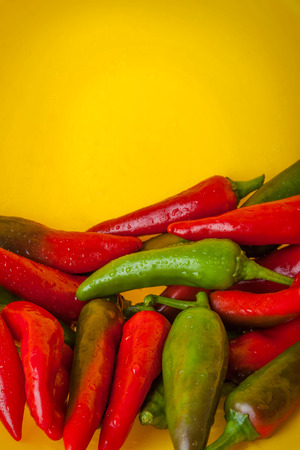 poignant: Red and Green Hot Peppers on the Yellow Background