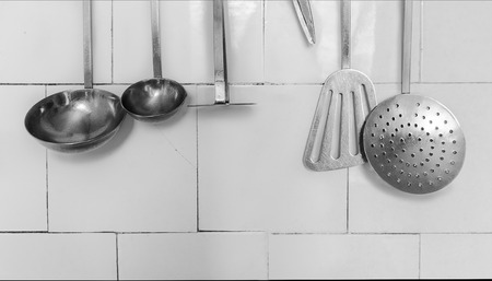Background Made with Kitchen Utensils Hanging on the White Tile photo