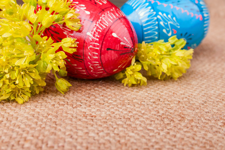 sheeted: Spring Yellow Flowers and the Easter Eggs on the Burlap Stock Photo