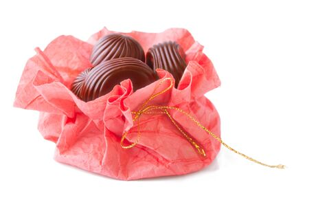 pack string: Chocolate Candies in Handmade Paper Pack with Golden String, Isolated on White