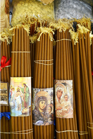 coptic orthodox: Jerusalem - April 30, 2017: Bundles of beeswax candles and incense for sale to pilgrims near the Church of the Holy Sepulchre, Christian Quarter. The bundles portray the Virgin and Christs miracles.