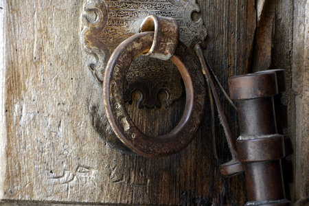 Jerusalem - April 30, 2017: Detail of the ironwork of the massive wooden door at the entrance to the Church of the Holy Sepulchre. The inscriptions, lock and knocker can be seen.
