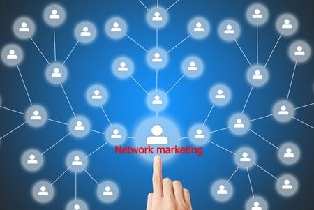 network marketing: La mano est� presionando el bot�n de la comercializaci�n de la red Foto de archivo