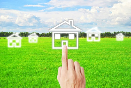 Finger is pressing on the house on meadow Stock Photo - 9729169