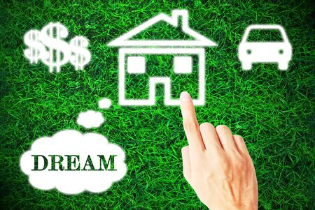 dream house: The hand is pressing the dream that on the grass