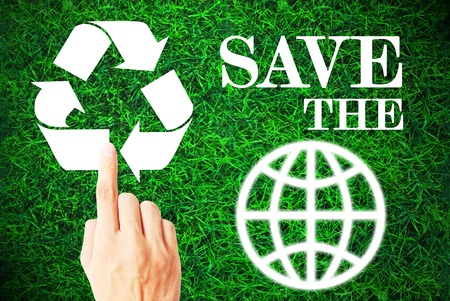The hand is pressing the recycle symbol with save the world in the grass photo