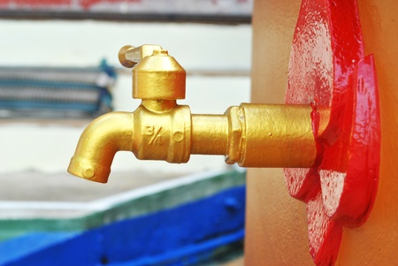 The golden water tap is in garden photo