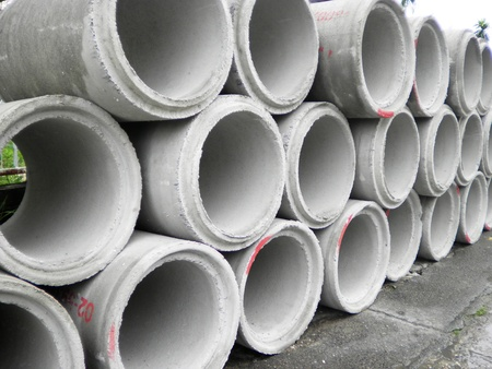 contruction: Concrete drainage pipe stacked on contruction site          Stock Photo