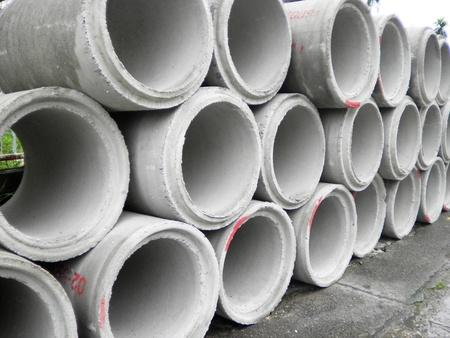 Concrete drainage pipe stacked on contruction site          Archivio Fotografico