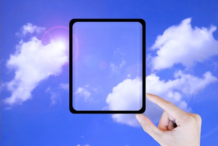 Hand touch the tablet on the sky photo