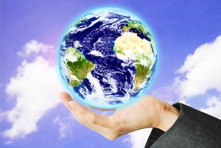 maketing: Hand hold the earth on the sky Stock Photo