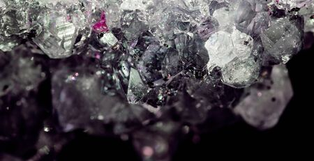 Gemstone Amethyst closeup as a part of cluster geode filled with rock Quartz crystals.