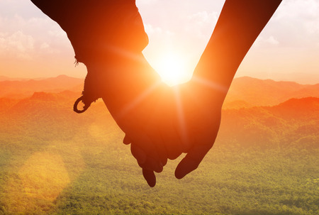 holding hands while walking: silhouettes on sunset of loving couple holding hands while walking at on Mount stacked. Stock Photo