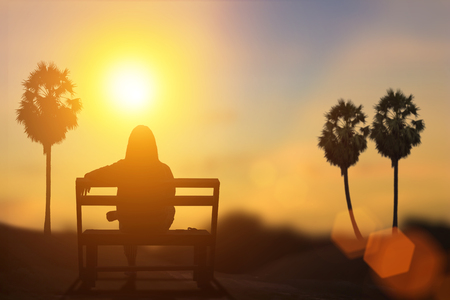 Silhouette of The waiting under the sun. Natural background blurring.warm colors and bright sun light.adult alone angry  betrothal break-up couple dark dead death destiny divorce feelings life trip. Stock Photo
