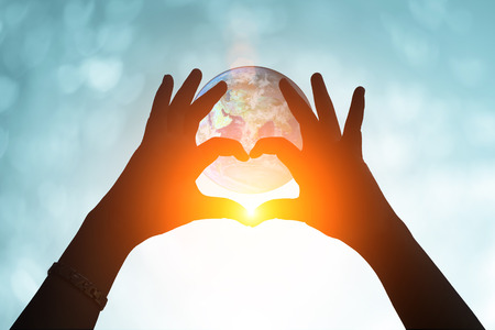 humble: earth and hands under a heart-shaped Silhouette .Blurred background of Valentines day concept. Pastel color tones.multicolored white  wallpaper.Elements of this image furnished by NASA . Stock Photo