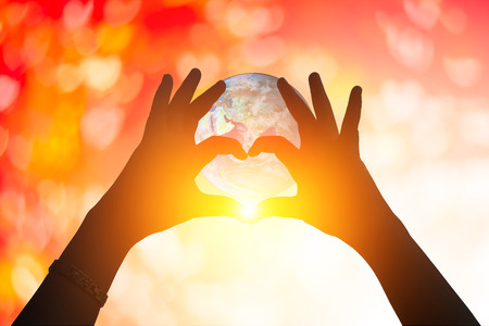 humble: earth and hands under a heart-shaped Silhouette .Blurred background of Valentines day concept. Pastel color tones.multicolored white  wallpaper.