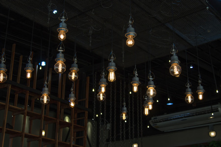Lighting on the chandelier in the lamplight and light bulbs hanging from the ceiling or lamps on the dark background . Stock Photo
