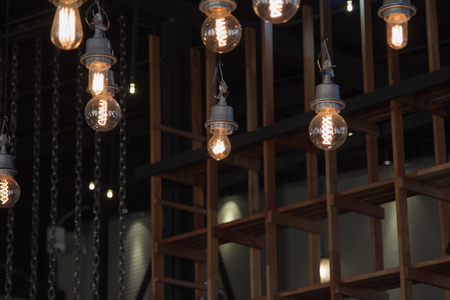 chandelier background: Lighting on the chandelier in the lamplight, light bulbs hanging from the ceiling, lamps on the dark background .Coffee Shop Decoration .