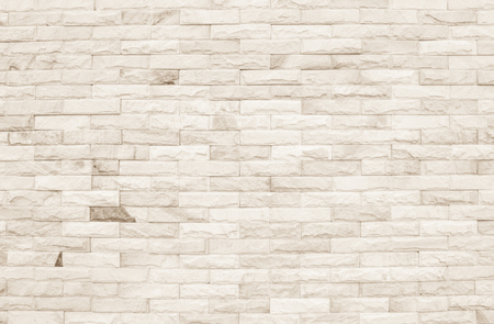 Cream and white brick wall texture background. Brickwork or stonework flooring interior rock old pattern clean concrete grid uneven bricks design stack. Stock Photo