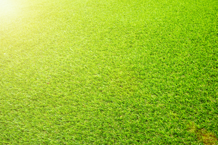 Beautiful Green artificial grass background vignette or the naturally walls texture Ideal for use in the design fairly. natural pattern texture fresh spring from golf course or soccer field.