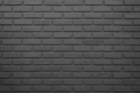 Black and grey brick wall texture background. Brickwork or stonework flooring interior rock old pattern clean concrete grid uneven bricks design stack.