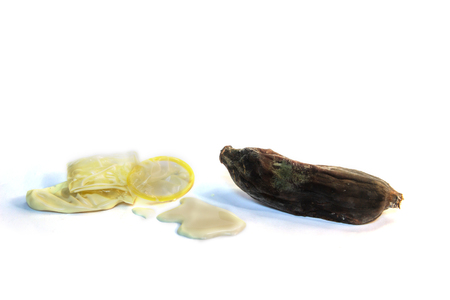 The contraceptive world symbol consists of condoms in semen and bananas withered instead of the penis on white isolated background. Space for text.
