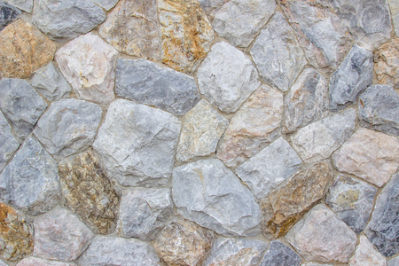 Background texture of Medieval natural stone wall textured background or boundary the Rock seamless abstract and fragment of a walls from a gray chipped stones ancient. Stockfoto