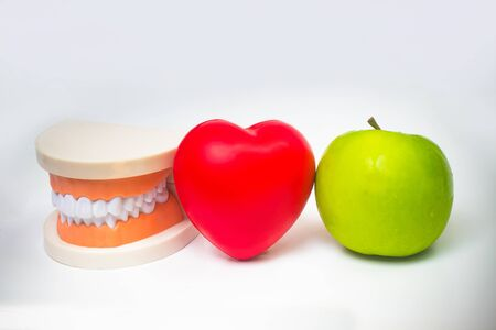False teeth denture against green granny smith apple. Dental prosthesis care. Denture and Apple in the hands of a doctor. Food and concept for dental care. Beautiful teeth. Prosthetic. False teeth. Archivio Fotografico