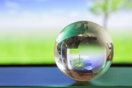 World globe crystal glass reflect in green wide grassland, tree and blue sky with clouds gloss on table beside the window. Global business and economy. Environmental conservation or ecology concept.