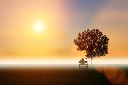 Silhouette of disabled person sit on chair under the big tree have sunset background. International Disability Day, Handicapped sport and Paralympics concept. Fog in clear nature, with copy space.