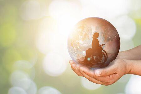 Behinderte Person im Rollstuhl in der Erde, die in menschlichen Händen in Richtung Zielstadt über aktive Arbeit hält. Internationaler Tag der Behinderung oder Paralympics für Behinderte. Autistic Awareness Day und Gesundheitskonzept.