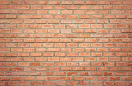 Old Orange brick wall concrete or stone texture background, wallpaper limestone abstract to flooring and homeworkBrickwork or stonework clean grid uneven interior rock old. Copy space.