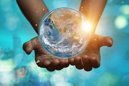 International Day of Forests and earth day concept: Hands holding blue earth globe over and green city background for World Environment Day.
