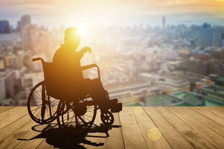 Disabled person silhouette with hand lift on wheelchair have sunset city background. International Disability Day or Handicapped sport or Paralympics. Challenge and Conquer success and health concept. Banque d'images