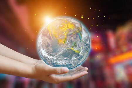 International Day of Forests and earth day concept. Hands holding blue earth globe in business hands on neon blurred background for world environment day, Ecology.