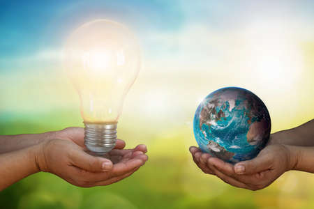 Developer hand holding light bulb and hand holding blue earth globe over blurred green nature background:f energy and earth day concept, World Environment Day. Banque d'images