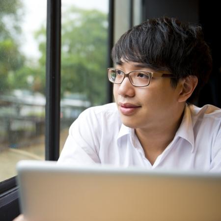 laptop asian: Un hombre mirando por la ventana