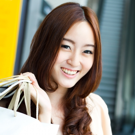 Happy young Asian woman shopping