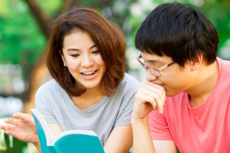 tutor: Los estudiantes leen un libro juntos en el parque.