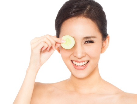 Asian woman holding cucumber slice to eye on white background 版權商用圖片