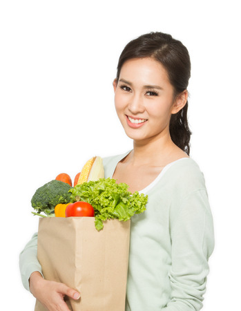 Happy young woman holding groceries bag