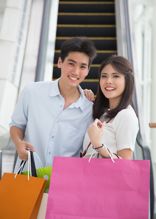 Happy young Asian couple shopping.