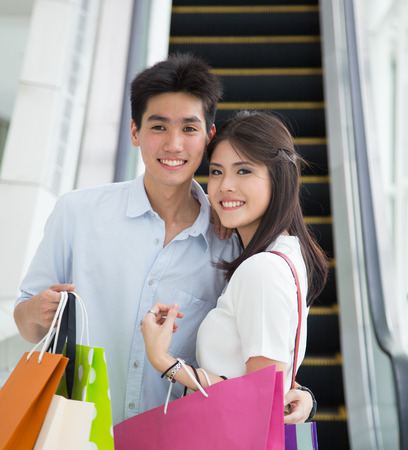 Happy young Asian couple shopping. photo