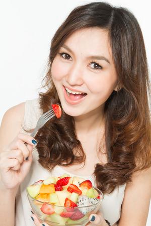 korean ethnicity: Woman eating fruit salad Stock Photo