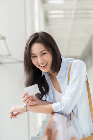 Asian woman showing her credit card
